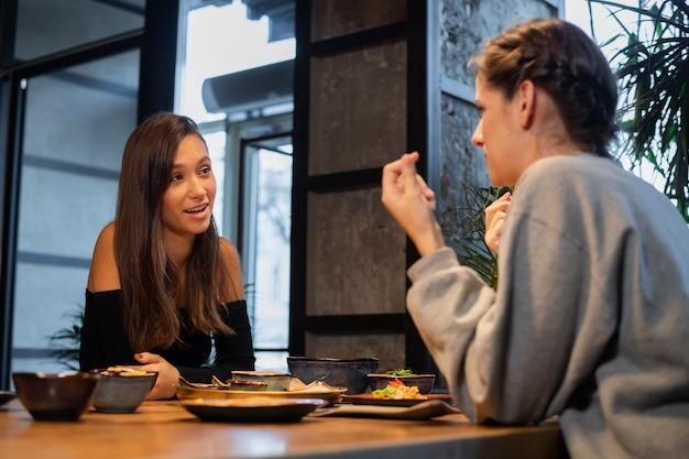 Junge mädchen plaudern in einem café im asiatischen stil
