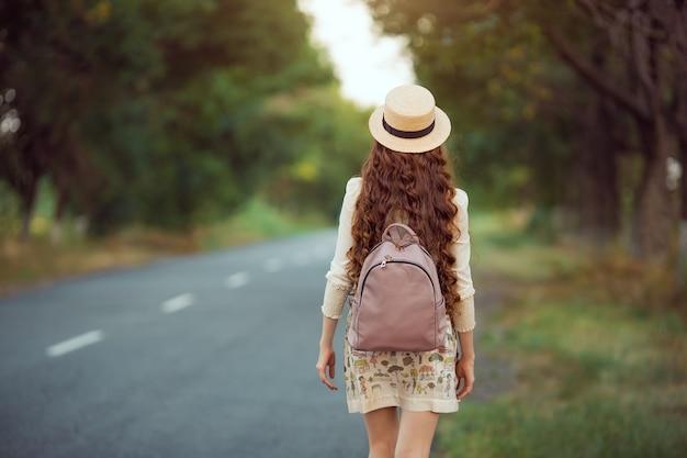 Junge mädchen reisende genießen die reise. glückliche frau, die auf der straße geht.