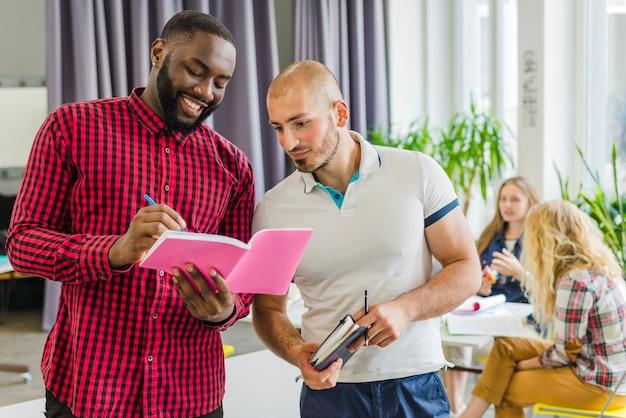 Junge männer arbeiten mit notizblöcken zusammen