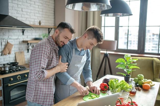 Junge männer, die am tisch in der küche stehen und frühstück vorbereiten.