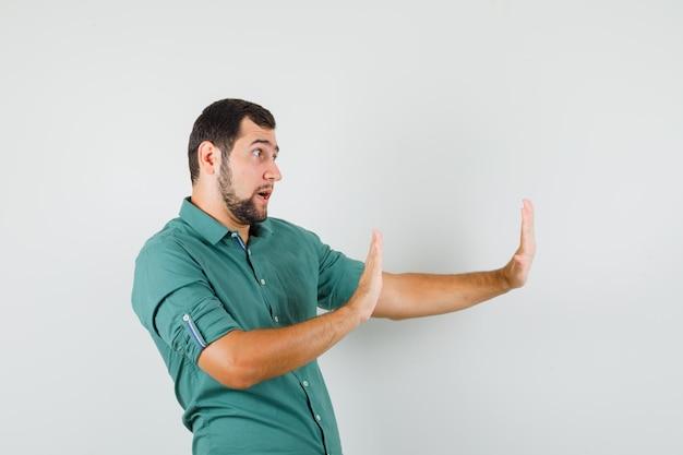 Junge männer, die arme heben, um etwas im grünen hemd abzulehnen und fokussiert zu schauen, vorderansicht.