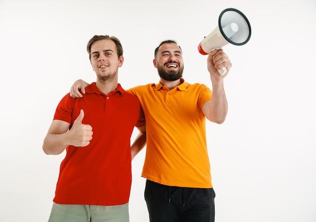 Junge männer, die bunte t-shirts tragen und megaphon auf weißer wand halten
