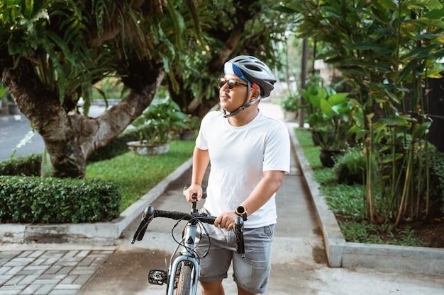 Junge männer, die fahrradhelme tragen, gehen an straßenfahrrädern vorbei