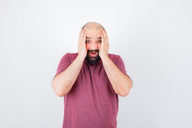 Junge männer, die hände auf wangen halten, während sie in rosa t-shirt schreien und alarmiert aussehen. vorderansicht.
