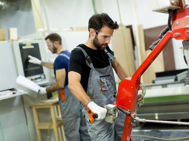 Junge männer, die in einer fabrik für die produktion von möbeln arbeiten