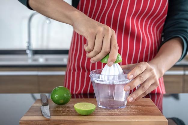 Junge männer, die limonade in der küche zusammendrücken