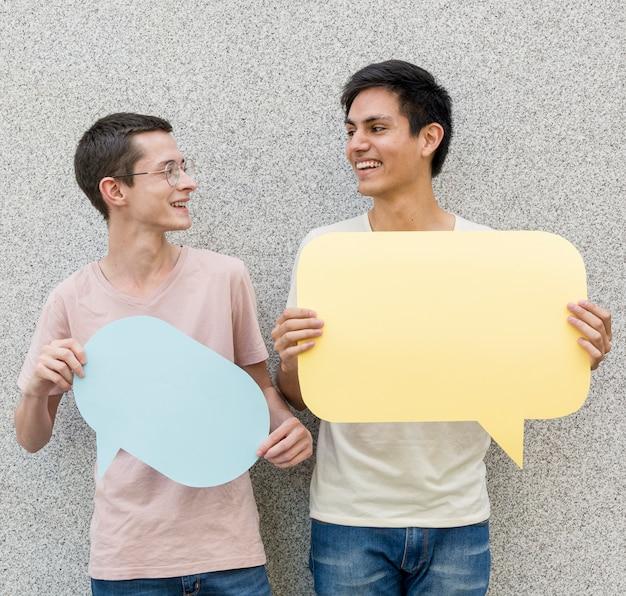 Junge männer, die spracheblasen halten
