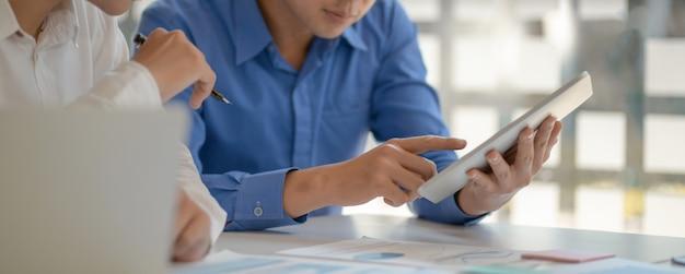 Junge männer, die zusammen an tablette arbeiten.