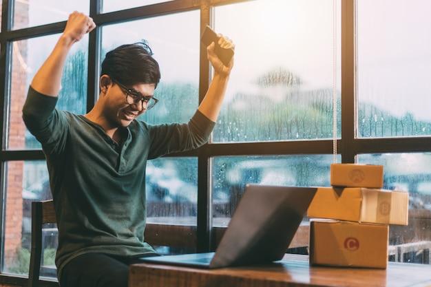 Junge männer freuten sich über den erfolg des online-verkaufs.