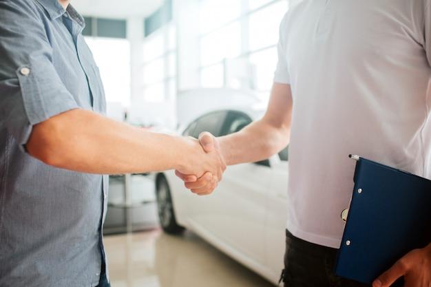 Junge männer händeschütteln vor weißem auto