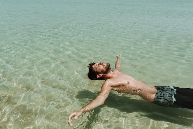 Junge männer im urlaub genießen das schwimmen auf einem kristallklaren wasserstrand von australien. entspannen sie sich und beruhigen sie sich