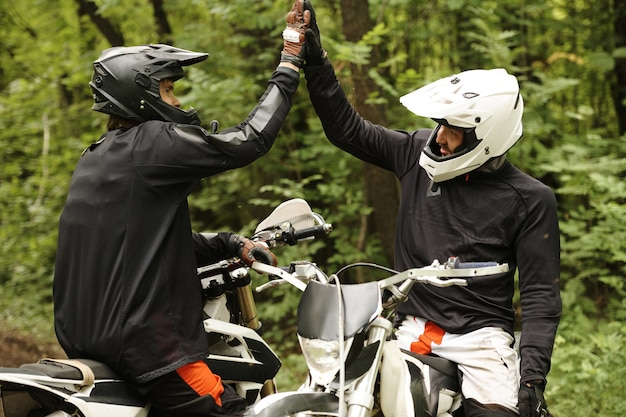 Junge männer in helmen sitzen auf motorrädern und geben high five, während sie sich während des rennens im wald gegenseitig unterstützen
