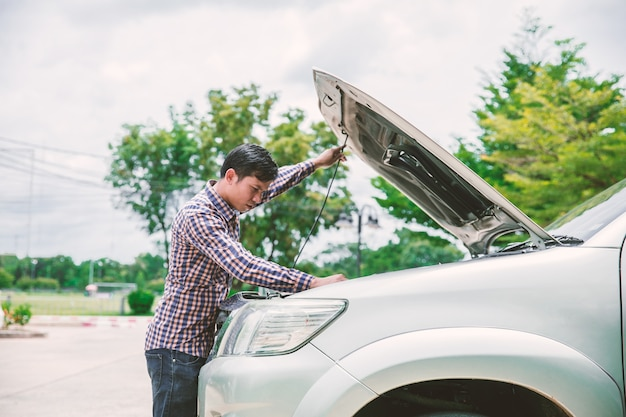 Junge männer nahe seinem defekten auto, das auf hilfe wartet.