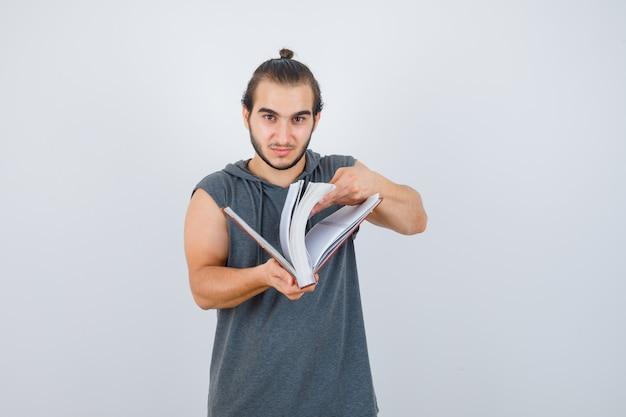Junge männer schauen durch buch in ärmellosem kapuzenpulli und sehen selbstbewusst aus. vorderansicht.