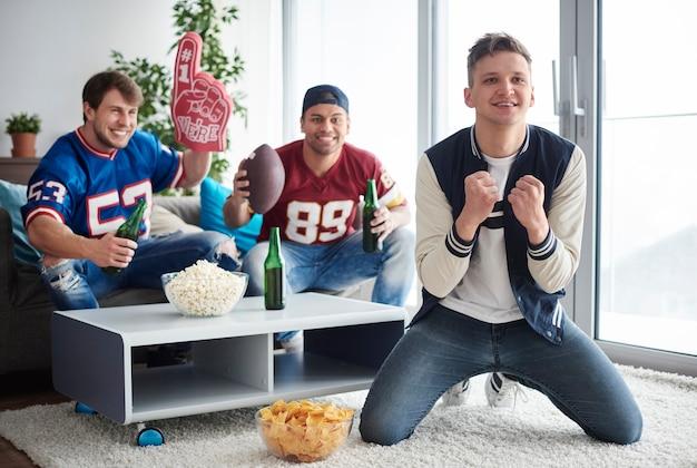 Junge männer schauen sich einen american-football-wettbewerb an