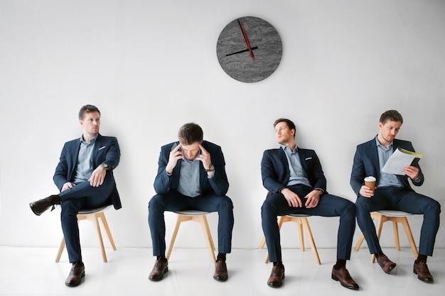 Junge männer sind anzüge, die auf weißen stühlen in einem raum sitzen