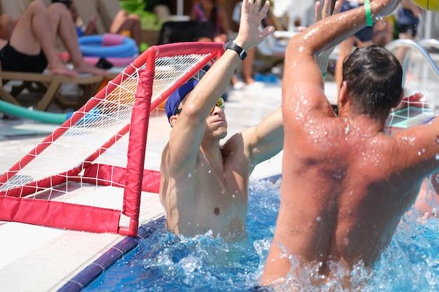 Junge männer spielen wasserball und schießen tor im schwimmbad