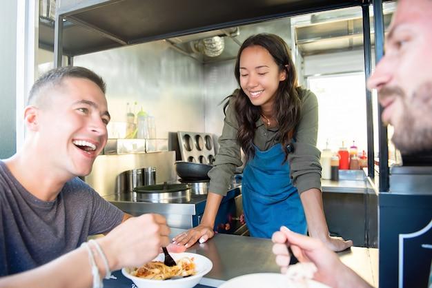 Junge männer sprechen und essen gerne teigwaren am food truck
