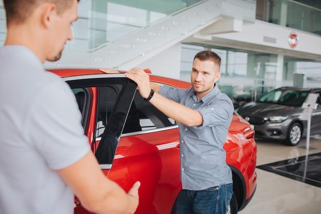 Junge männer stehen neben dem roten auto und halten die haustür offen