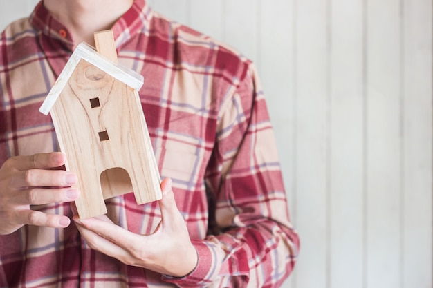 Junge männer tragen das rote ginghamhemd, das miniaturhausmodell, immobilieninvestitionskonzept, copyspace hält