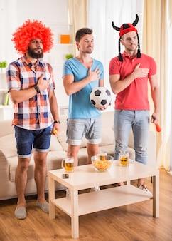 Junge männer trinken bier, essen pizza und jubeln dem fußball zu