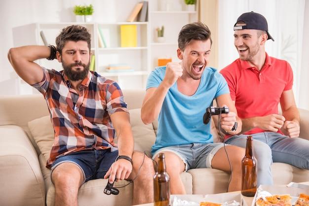 Junge männer trinken bier, essen pizza und spielen spielstation