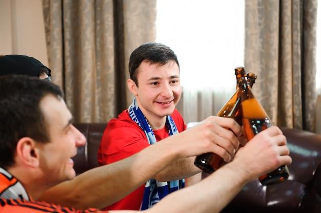 Junge männer trinken bier, essen pommes und wurzeln für den fußball