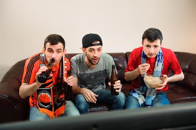 Junge männer trinken bier, essen pommes und wurzeln für fußball.