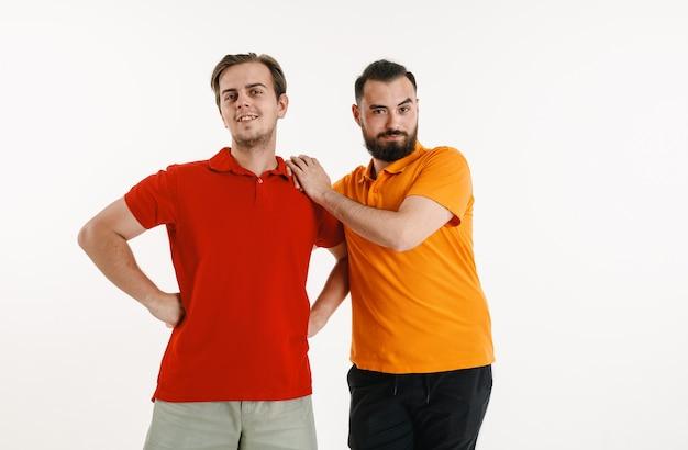 Junge männer trugen in lgbt-flaggenfarben lokalisiert auf weißer wand. kaukasische männliche modelle in hellen hemden. sieh glücklich aus, lächle und umarme dich. lgbt-stolz, menschenrechte und wahlkonzept.