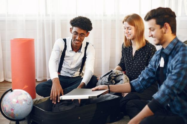 Junge männer und frauen, die sich auf eine reise vorbereiten. reisende, die kleidung und gepäck in einen koffer packen.