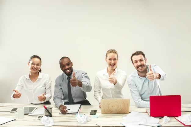 Junge männer und frauen sitzen im büro und arbeiten an laptops. emotionskonzept