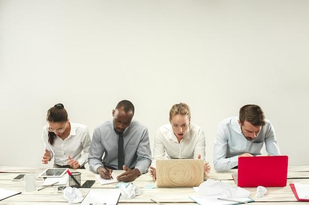 Junge männer und frauen sitzen im büro und arbeiten an laptops.