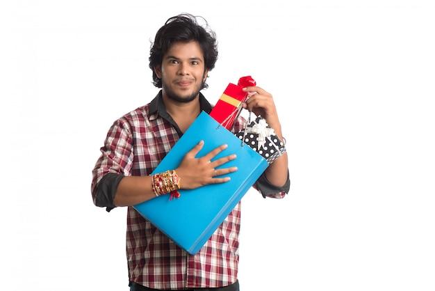 Junge männer zeigen rakhi auf seiner hand mit einkaufstüten und geschenkbox anlässlich des raksha bandhan festivals.