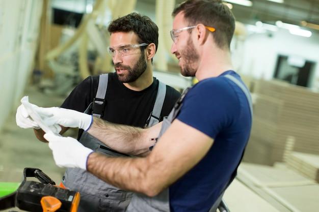 Junge männliche arbeiter arbeiten in einer fabrik für die produktion von möbeln