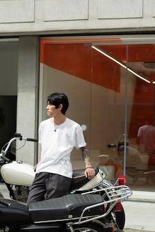 Junge männliche barista mit tätowierungen, die vor dem öffnen vor dem kaffeehaus warten