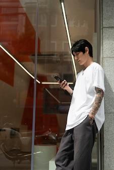 Junge männliche barista mit tattoos, die vor dem kaffeehaus vor dem öffnen und verwenden des smartphones warten