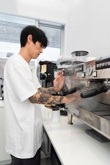 Junge männliche barista mit tattoos mit der kaffeemaschine bei der arbeit