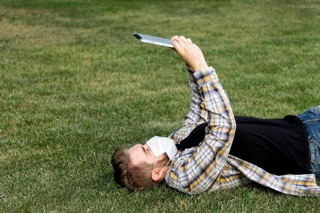 Junge männliche browsing-tablette im freien