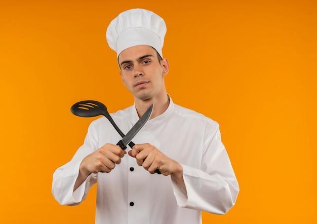 Junge männliche coole tragende kochuniform, die schöpflöffel und messer in seiner hand auf isolierter gelber wand kreuzt