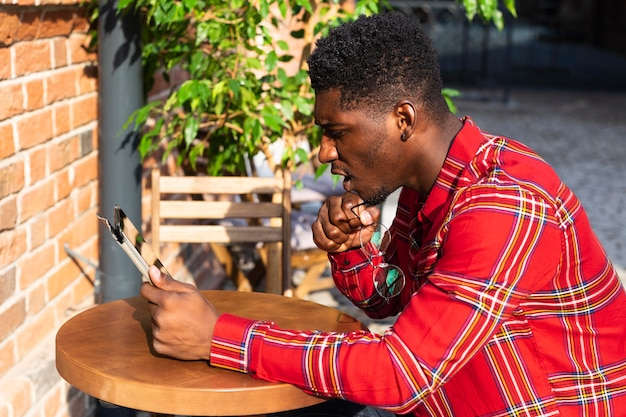 Junge männliche erwachsene lesung an einem tisch
