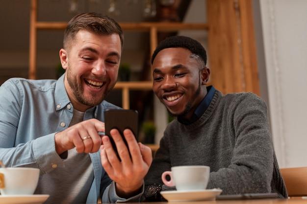 Junge männliche freunde, die auf mobile schauen