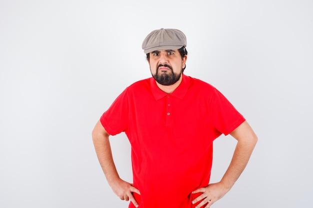 Junge männliche händchen haltend an der taille in rotem t-shirt, mütze und unzufrieden aussehend, vorderansicht.