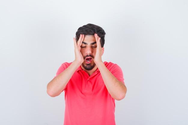 Junge männliche händchen haltend auf dem gesicht in rosa t-shirt und erschöpft aussehend, vorderansicht.