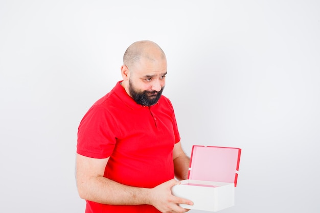 Junge männliche holding geöffnete geschenkbox im roten t-shirt und schüchtern, vorderansicht.