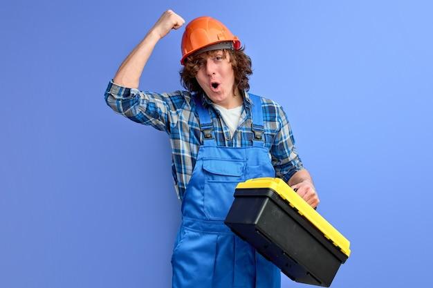Junge männliche ingenieure in blauen overalls, die an einen orangefarbenen helm klopfen, sorgen dafür, dass die mitarbeiter gut geschützt arbeiten