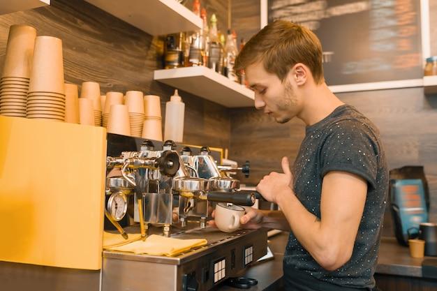 Junge männliche kaffeestubearbeitskraft, die kaffee mit maschine macht