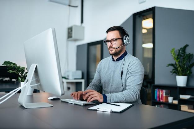 Junge männliche kundenbetreuung mit dem kopfhörer, der an dem computer arbeitet.