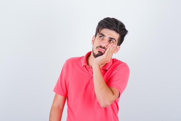 Junge männliche lehnende wange auf der handfläche in rosa t-shirt und nachdenklich aussehend. vorderansicht.