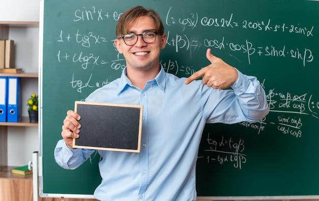 Junge männliche lehrer mit brille, die eine kleine tafel hält, die mit dem zeigefinger darauf zeigt und lächelnd selbstbewusst in der nähe einer tafel mit mathematischen formeln im klassenzimmer steht
