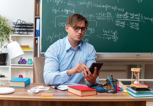 Junge männliche lehrer mit brille, die eine nachricht mit dem smartphone eingeben und selbstbewusst auf der schulbank sitzen, mit büchern und notizen vor der tafel im klassenzimmer
